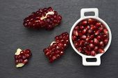 Pomegranate Seeds In The White Bowl On Dark Background. Organic Fresh Pomegranate In White Bowl On T poster