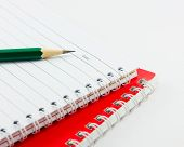 Pencil On The Blank Notepad Isolated With White Background