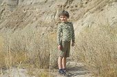 curious boy hikes in badlands