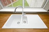 White ceramic kitchen sink with solid wooden worktop