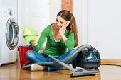 Young woman cleaning at home, she has a cleaning day and using a vacuum cleaner cleaning products an