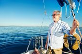 stock photo of life-boat  - confident captain of sail boat standing and looking out to sea - JPG