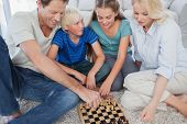 Portrait of a cheerful family playing chess lying on a carpet