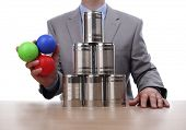 Businessman holding balls for tin can alley style business challenge concept for competition, chance