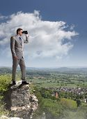 Businessman standing at the edge of a cliff looking through binoculars concept for job search, business vision or looking to the future