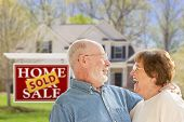 picture of retirement age  - Happy Affectionate Senior Couple Hugging in Front of Sold Real Estate Sign and House - JPG