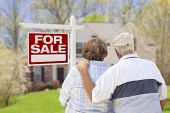 Happy Senior Couple Front of For Sale Real Estate Sign and House.