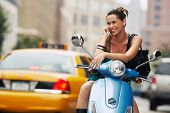 Young happy woman using mobile phone on moped