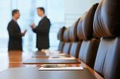 stock photo of negotiating  - Side view of two blurred businessmen talking in conference room - JPG