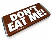 The words Don't Eat Me on a chocolate candy bar wrapper telling you this is unhealthy junk food that you should not consume if you want to lose weight and fat