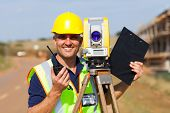 stock photo of theodolite  - happy senior land surveyor with tacheometer on construction site - JPG