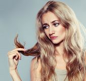 pic of split ends  - Young woman looking at split ends - JPG