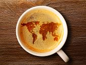 world map on cup of fresh espresso on table, view from above