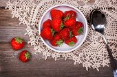 A bowl of fresh ripe strawberries on lace tablecloth and rustic wood table. Vintage effect with inte
