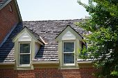 stock photo of gabled dormer window  - Two dormers in roof with wood shingles on a brick townhouse - JPG
