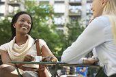 Dos colegas multiétnicas sentado en el café calle