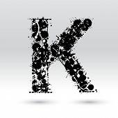 Letra K, formada por manchas de tinta