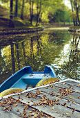 stock photo of pontoon boat  - Blue boat on lake in autumn season - JPG
