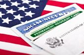 picture of illegal  - United States of America social security and green card with US flag on the background - JPG