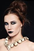 Portrait of young beautiful woman with black lipstick and gothic skull necklace