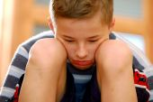 stock photo of sad boy  - Portrait of young boy sitting sadly - JPG