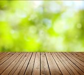 stock photo of foliage  - Empty wooden deck table with foliage bokeh background - JPG