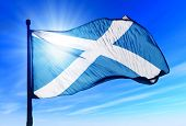 image of light-pole  - Scotland flag waving on the wind on the sky - JPG
