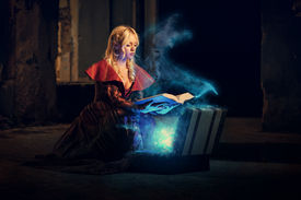 picture of paranormal  - Young beautiful witch in a dark room reads a magical book and conjurer - JPG