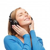 music and technology concept - smiling young woman with closed eyes listeting to music with headphon