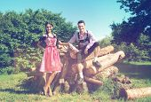 Image of loving couple in traditional Bavarian clothes posing together in countryside