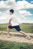 Man limbering up before exercise stretching his leg muscles to increase mobility as he stands on a t