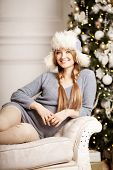 Beautiful young woman  at the Christmas tree. Beautiful girl celebrates Christmas