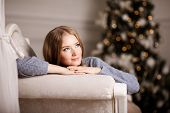Beautiful young woman near the Christmas tree. Beautiful girl celebrates Christmas