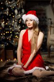 Young beauty smiling santa woman near the Christmas tree. Fashionable luxury girl celebrating New Ye