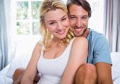 Cute young couple relaxing on bed smiling at camera at home in the bedroom