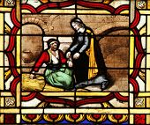 PARIS, FRANCE - NOV 11, 2012: Saint Vincent de Paul helps a prisoner, stained glass from Church of S