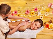 Woman getting stone therapy massage in wooden spa.