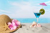 Blue cocktail on the beach with a sunhat and sea shells