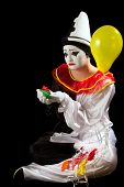 Crying pierrot clown holding exploded balloons in his hand