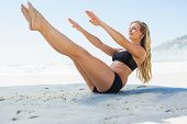 stock photo of pilates  - Fit blonde in core balance pilates pose on the beach on a sunny day - JPG