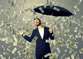 happy businessman with umbrella standing under money rain and looking up