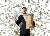 smiley glad businessman standing under money rain, holding big paper bag and showing dollar's