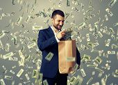 smiley glad businessman standing under money rain and putting dollar's in the paper bag