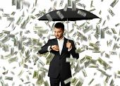serious businessman with black umbrella standing under money rain and looking at watch