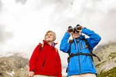 Senior hikers with binoculars