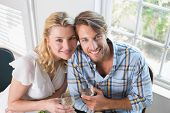 Cute smiling couple enjoying white wine together at home in the dining room