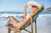 Pretty woman relaxing in deck chair on the beach on a sunny day