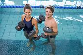 Man and woman standing with foam dumbbells in the pool at the leisure center