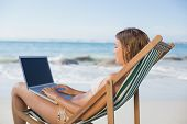 Woman relaxing in deck chair on the beach using laptop on a sunny day
