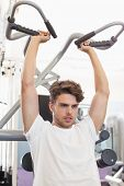 Fit focused man using weights machine for arms at the gym